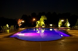 inground pool at night with pool lights lit